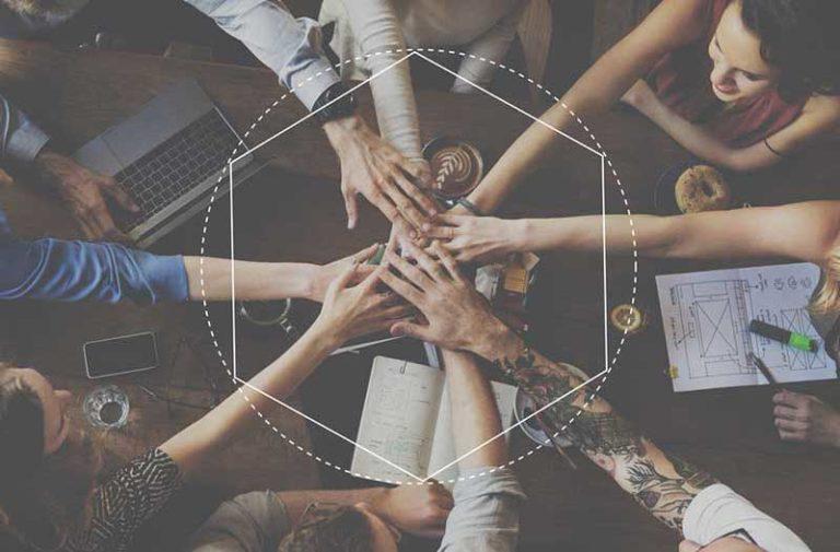 Mannen en vrouwen aan tafel strekken handen naar elkaar uit