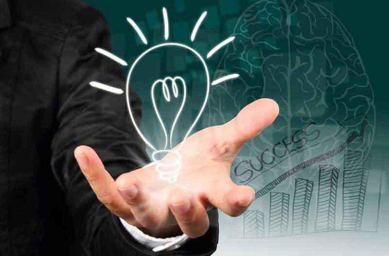 Een gloeilamp die boven een hand van een persoon in een pak zweeft, met een pictogram van een menselijk brein op de achtergrond