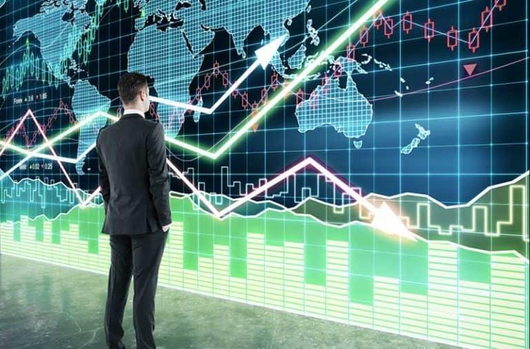 Man in pak staat voor een grote digitale wereldkaart met grafieken en lijnen