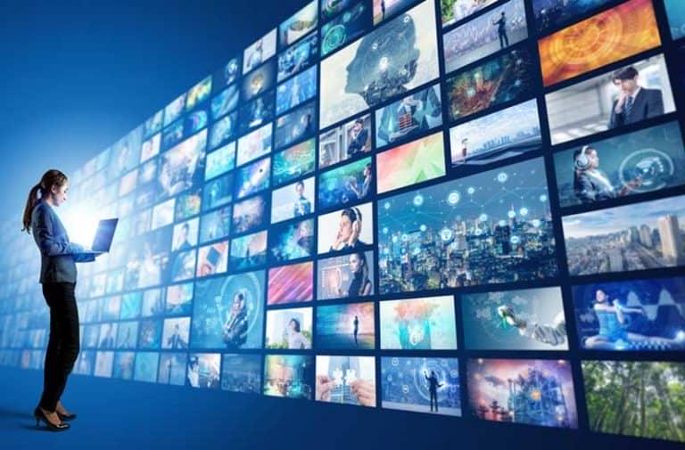 Een vrouw met een laptop staat voor een levensgroot scherm met allerlei filmafbeeldingen