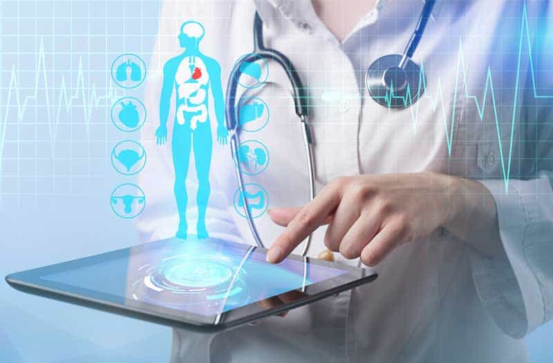 Lady in white lab coat holding a tablet with a digital image of a person and health-icons floating above it