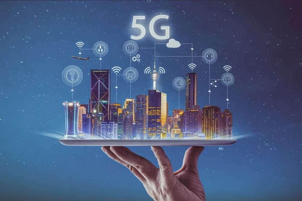 Een hand die een holografisch beeld van een nachtelijke stad vasthoudt. Er staat 5G boven geschreven en zweven verschillende pictogrammen boven.