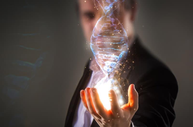 Man in zwart pak strekt hand uit waarboven een hologram van een DNA-streng zweeft