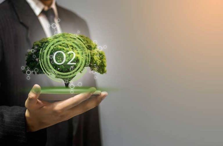 """Man in pak strekt hand uit met daarin een miniatuurboompje met """"CO2"""""""