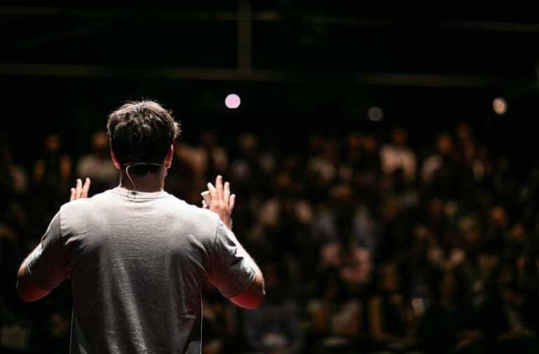 Een man in een grijs shirt spreekt een zaal met mensen toe