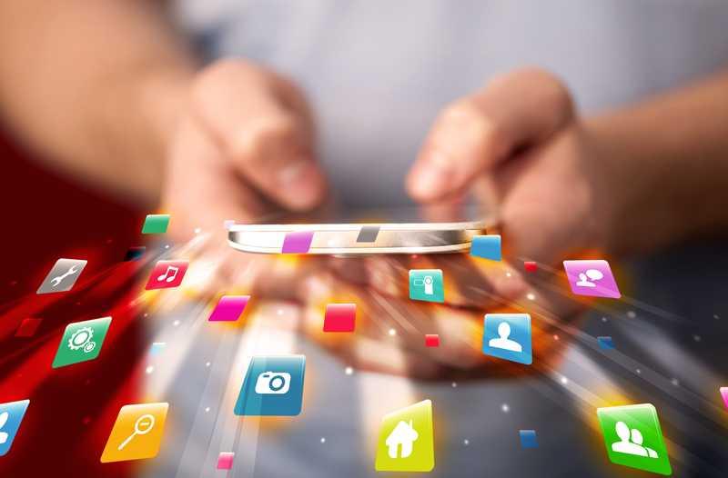 Een persoon typt op een smartphone waarboven een digitale overlay zweeft met gekleurde pictogrammen