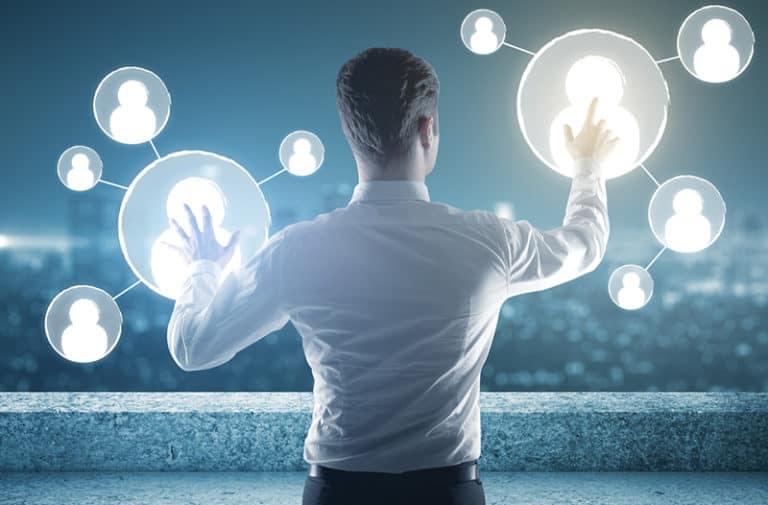 Man in een wit shirt wijst met beide handen naar zwevende, cirkelvormige, digitale afbeeldingen