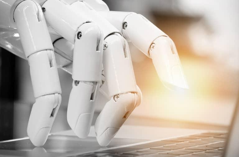 Witte robotvingers typen op het keyboard van een laptop