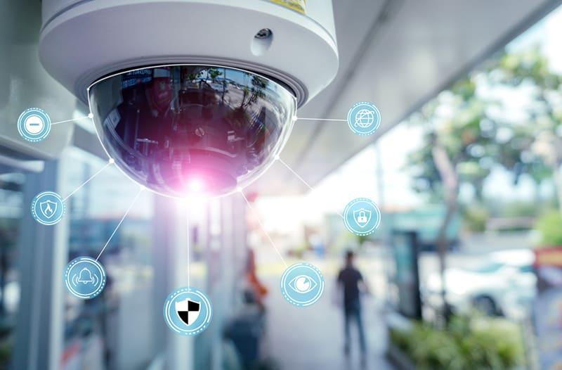 Ronde glazen surveillancecamera hangt buiten aan een plafond van een gebouw