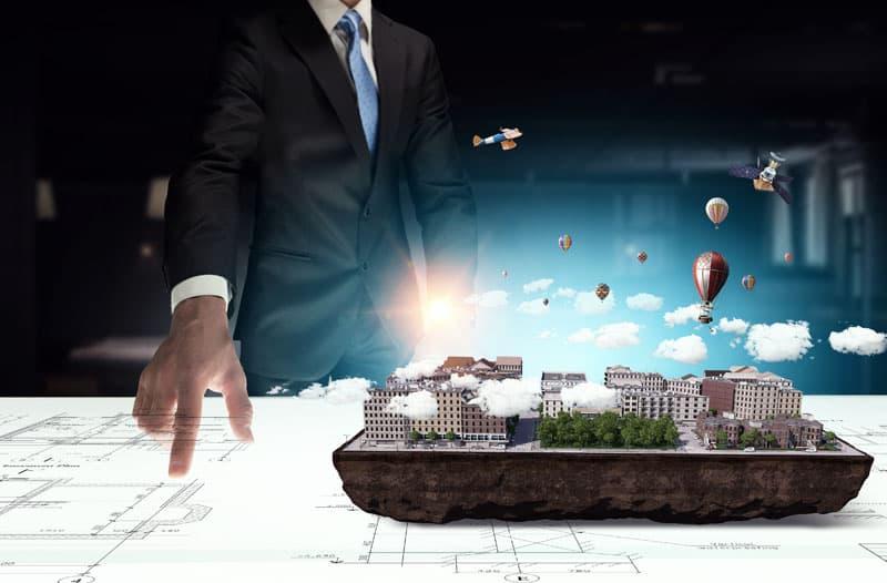 Een man in een pak staat aan een tafel met bouwtekeningen waarboven een hologram zweeft van een stad met luchtballonnen