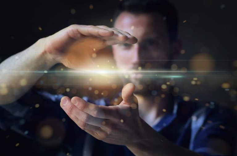 Man met uitgestrekte handen waartussen een hologram zweeft van digitale punten