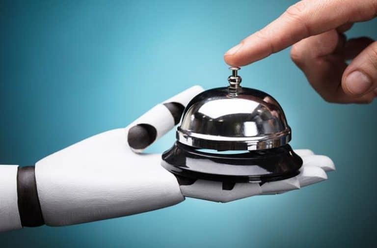 Mensenhand drukt op een bel die door een witte robothand vastgehouden wordt