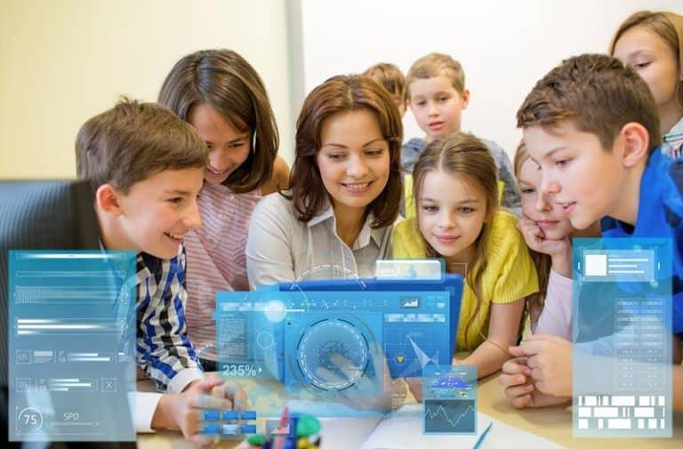 Kinderen en een lerares zitten in een klas en kijken naar digitale schermen