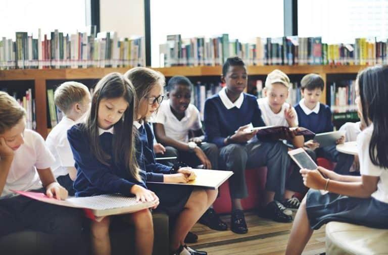 Kinderen in blauw-witte schooluniformen lezen boeken in een bibliotheek