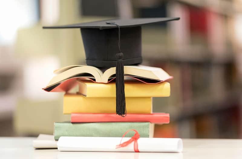 Een stapel studieboeken met daar bovenop een zwarte afstudeerhoed