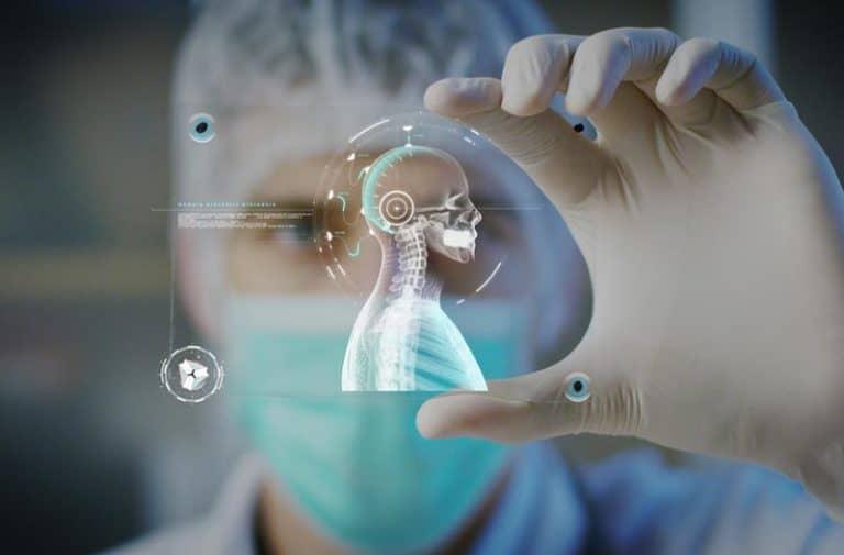 Man met medisch mondkapje en haarnetje houdt een hologram van een menselijk skelet tussen zijn duim en wijsvinger