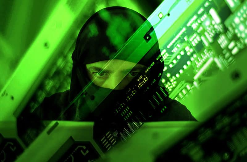 Green computer screen with a reflection of a man in a black hoodie