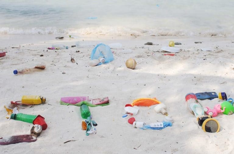 Wit zandstrand met plasticafval dat het woord STOP vormt