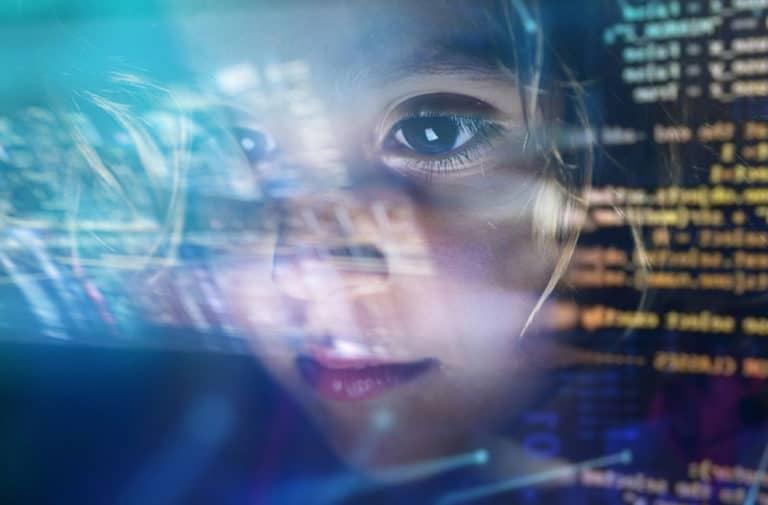 Het gezicht van een kind naast een scherm met computercode.