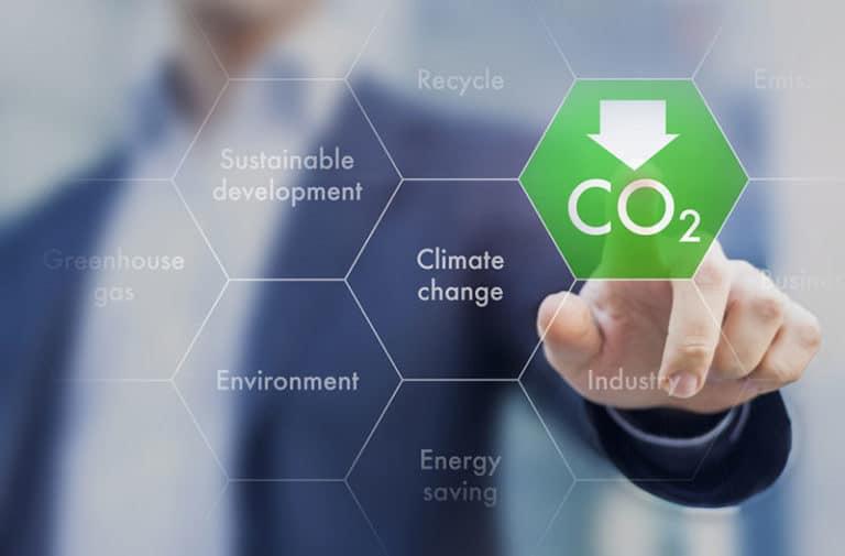 Een transparant zeshoekig raster met een wazig beeld van een persoon op de achtergrond. Elk veld in het raster bevat teksten over klimaatverandering en CO2 is in groen gemarkeerd.