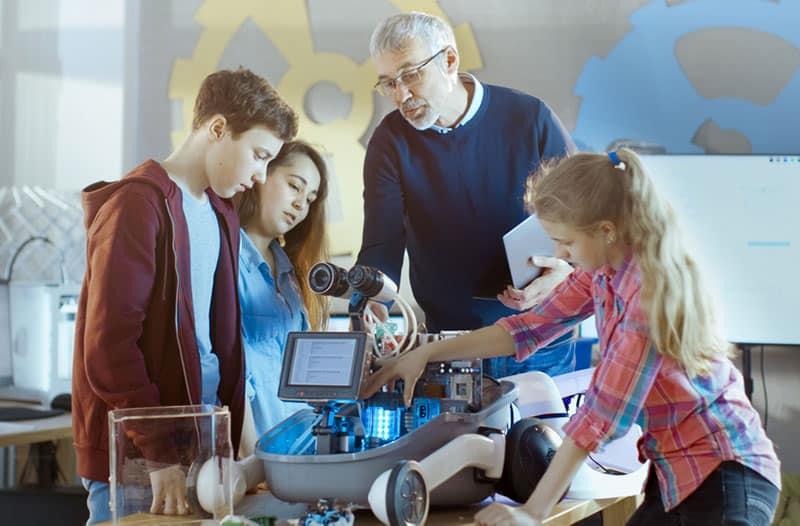 Een docent staat bij een groep leerlingen te kijken naar hoe ze een robot bouwen