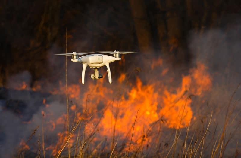 Witte drone vliegt boven een brandend bos