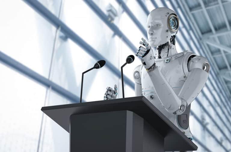 Een robot staat op een podium achter een microfoon en houdt een speech