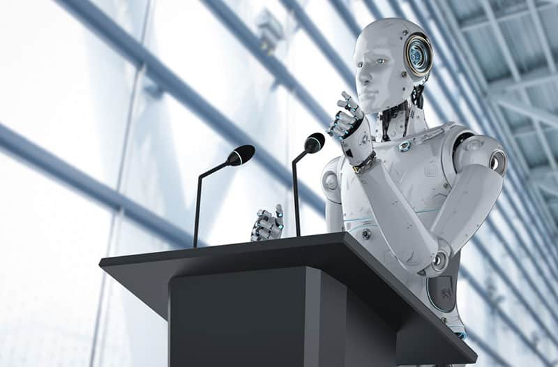 A robot standing behind a podium and delivering a speech