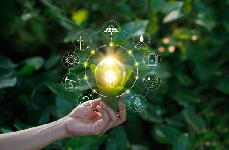 Een persoon staat voor een groene struik en strekt een arm uit waarboven een digitale bol zweeft met diverse iconen