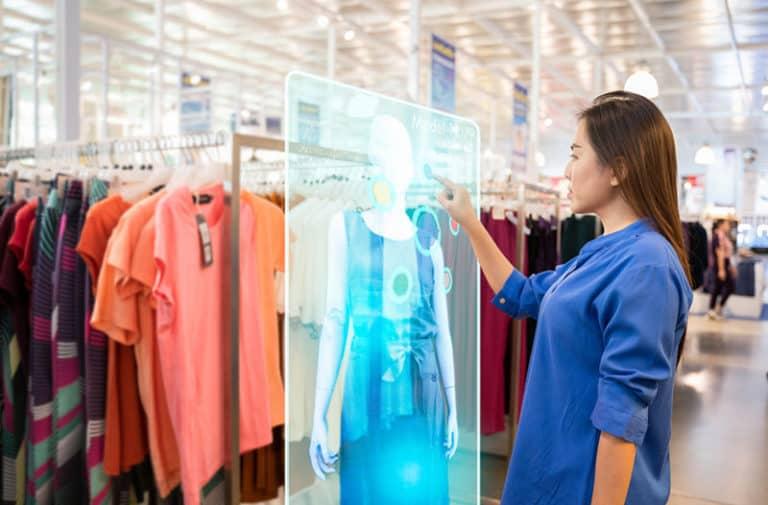 Vrouw met lang bruin haar en een blauwe jurk staat in een kledingzaak en tikt een virtuele passpiegel aan