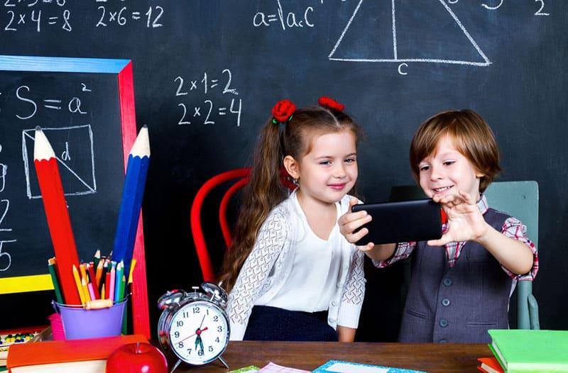 Twee jonge kinderen zitten voor een schoolbord in een klaslokaal en kijken op een smartphone.