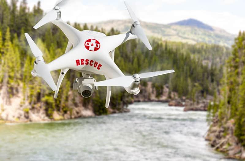 Witte reddingsdrone vliegt over een natuurlandschap met een rivier en bomen