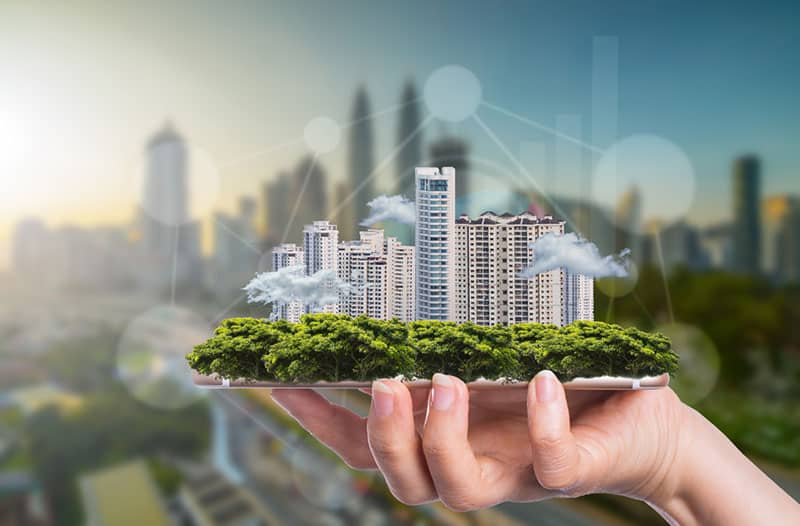 Een hand houdt een kleine maquette vast van een piepklein stadje met wolkenkrabbers en groene bomen