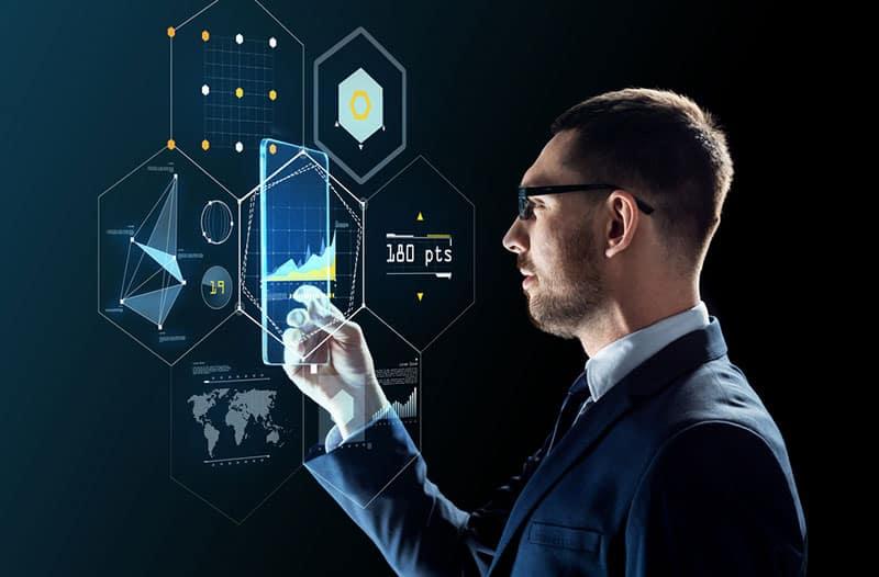 Een man in een donkerblauw pak bedient een virtueel transparant scherm met verschillende grafieken op de achtergrond.