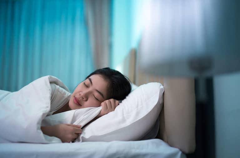Vrouw met donker haar ligt in een bed met wit beddengoed te slapen