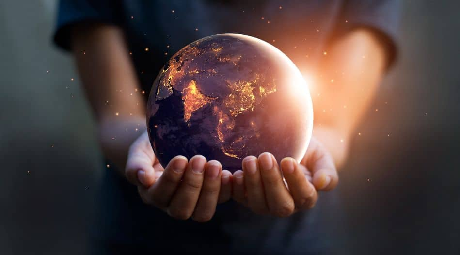 Two human hands holding the earth by night and by day