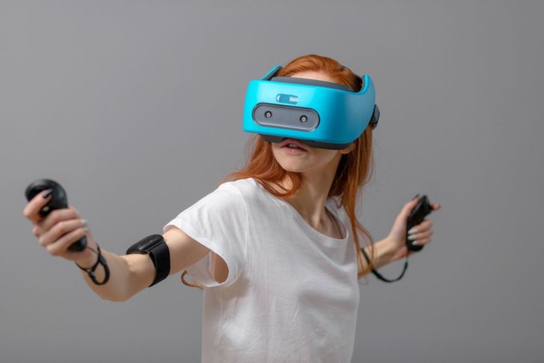 Girl with red hair and blue VR headset lifting her arm