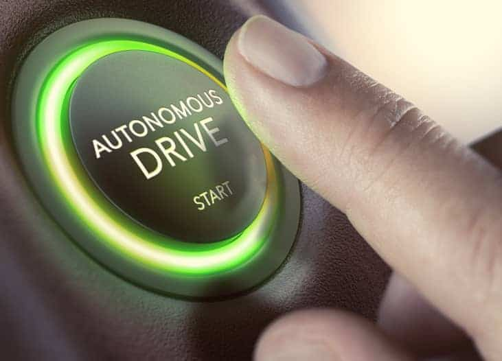 Finger pushes on round button with the text 'autonomous drive'