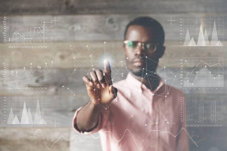 Donkere man met bril wijst naar een digitaal scherm met verlichte afbeeldingen