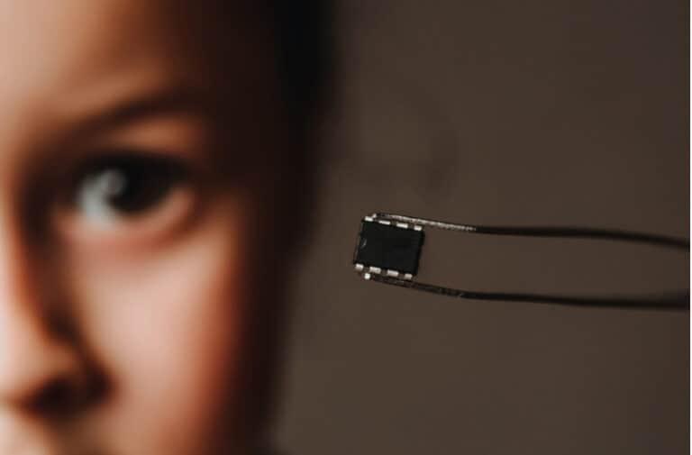 Vrouw houdt een zwarte microchip vast met een pincet