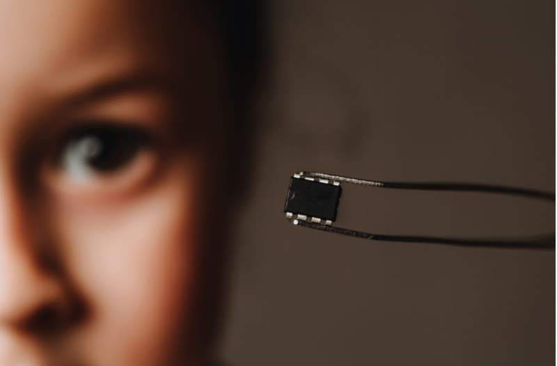 Woman holding a black microchip with a pair of tweezers