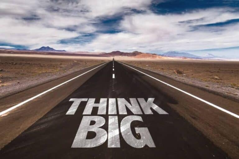 Een weg door de woestijn waarop de woorden 'Think Big' geschilderd zijn