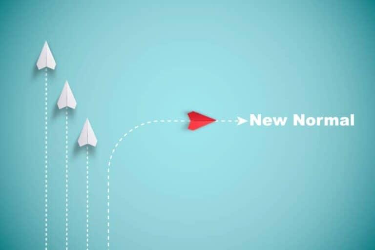 Drie witte papieren vliegtuigjes en één rode met de woorden 'now' en 'normal'