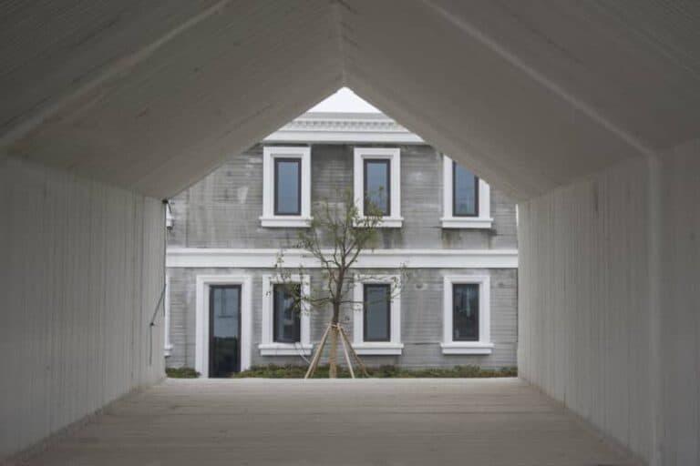 De binnenkant van een 3D-geprinte woning waarachter een andere woning zichtbaar is