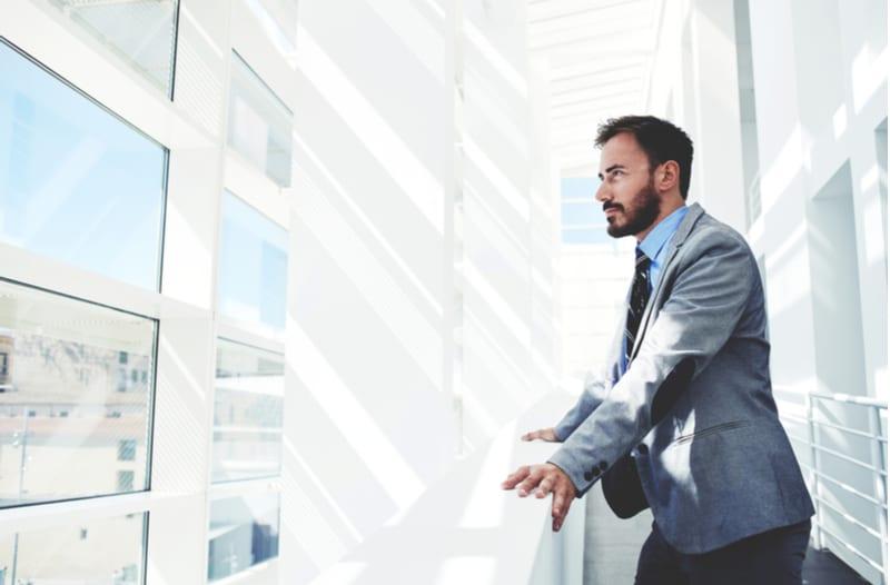 Jonge zakenman staart uit het raam van zijn kantoor
