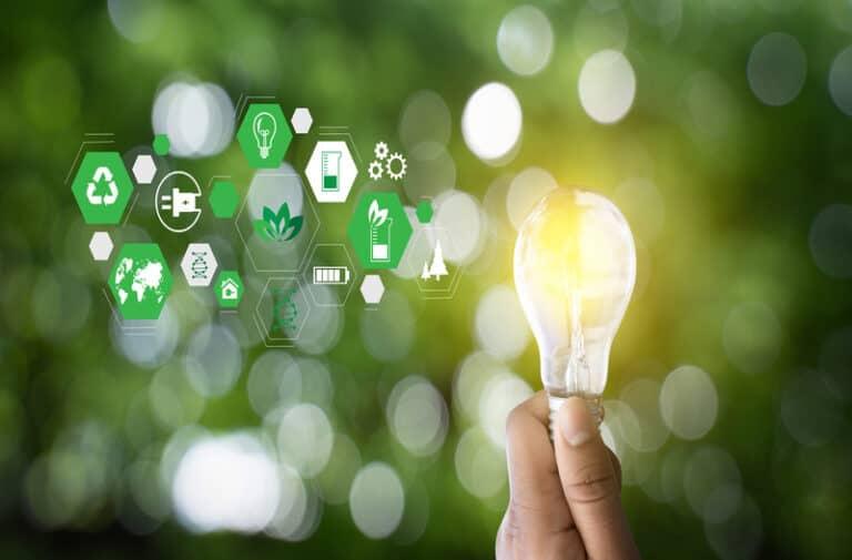 Een hand raakt een gloeilamp aan, omringd door zwevende iconen die duurzame energie vertegenwoordigen