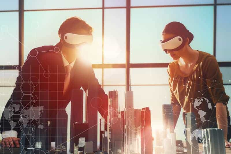 Two business professionals working on a property development project wearing VR headsets