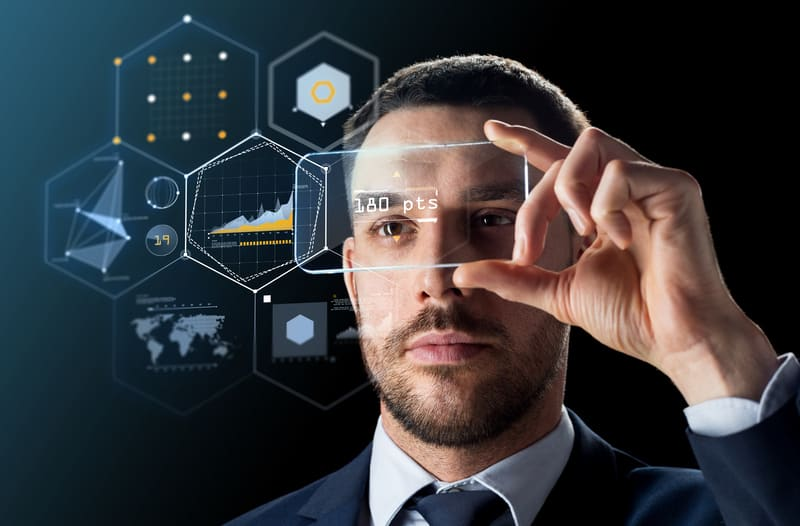 Man in suit holding a virtual smartphone with digital infographics floating in the background