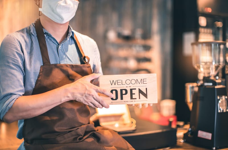 A man wearing an apron and a face mask sitting on the counter in a coffee shop