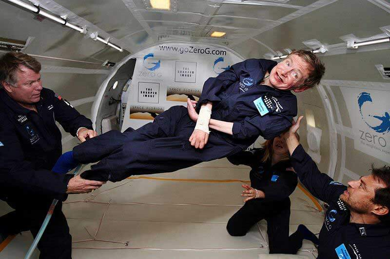 Two men and a woman holding Stephen Hawking who's floating in a Zero G plane